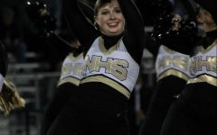Senior Evie Bartley shakes her poms over her head while preforming at the home varsity football game on Sept. 11.