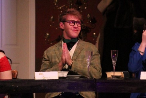 Senior Ezekiel Thompson smiles as Mr.Green at the dinner table in the March production of Clue.