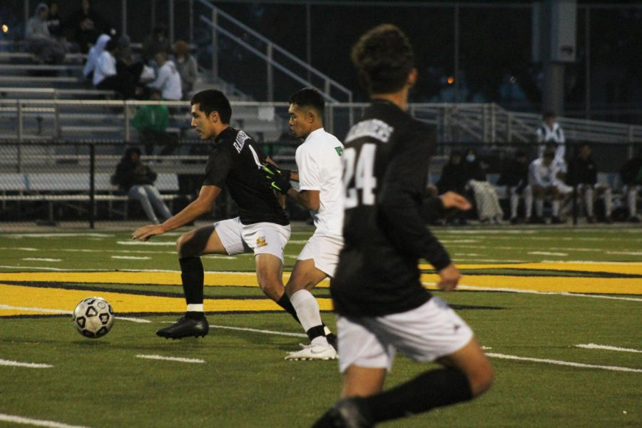 Junior Miguel Parga dribbles the ball away from his opponent.