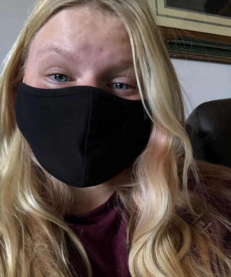 Junior Derica Mercer poses in her favorite mask, an all black mask from the medical apparel brand Jaanuu.