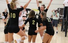 The varsity volleyball team celebrates after a successful match.