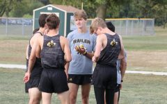 Senior Luke Schmidt (gray) talks to various members of the cross country team at the Oct. 3 home meet.