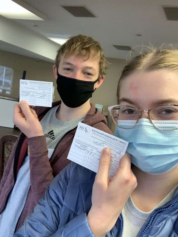 Juniors Ben Friesen Guhr (left) and Daisy Buller (right) pose with their COVID-19 Vaccination Record Card after receiving their first dosage of the vaccine.