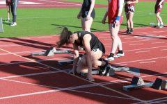 Sophomore Gracie Hendrickson runs through a start before her race.