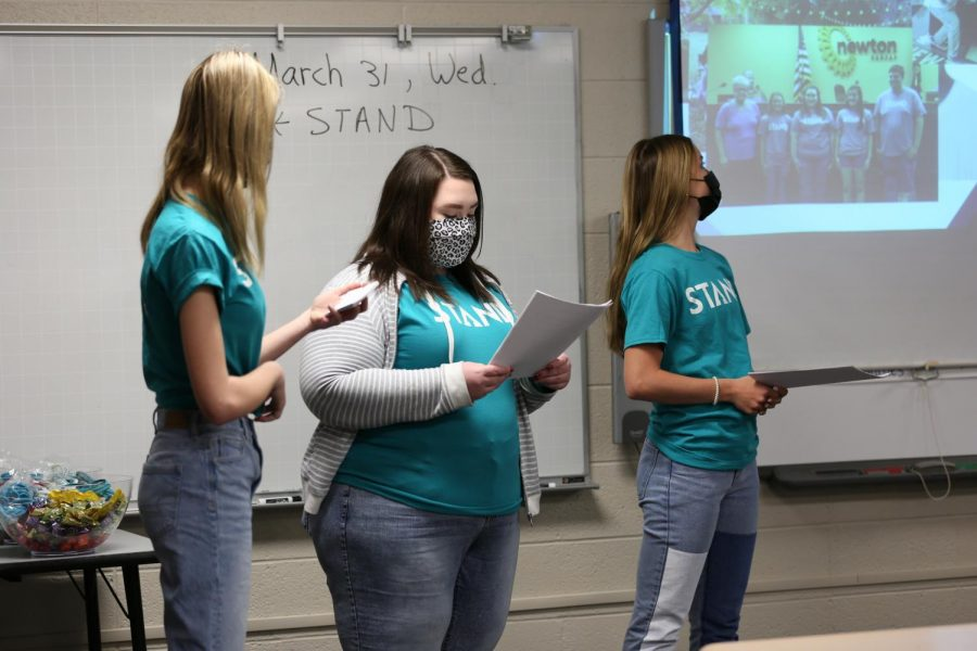 Junior Savannah Hunsucker reads off a piece of paper while presenting with junior Hallie Watkins and sophomore Gracie Hendrickson.