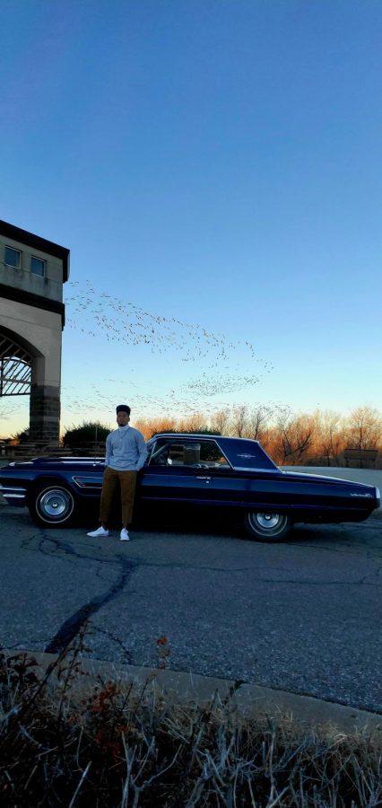 With a sunset as his backdrop, senior Elijah Edwards poses with his  1965 Pontiac Thunderbird.