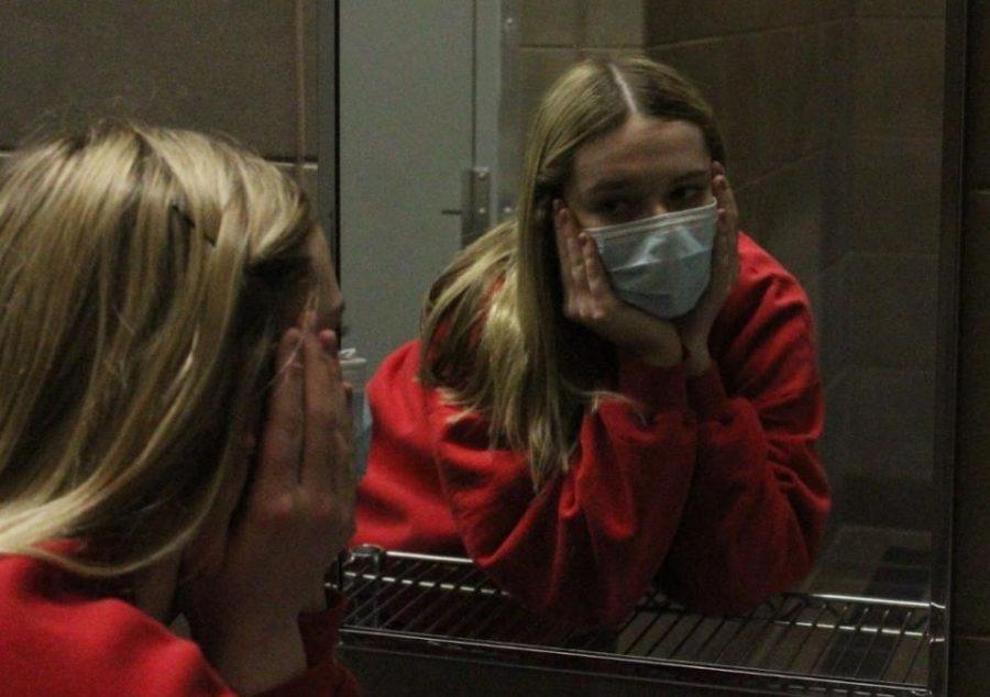 Junior Elly Green examines herself in the bathroom mirror.