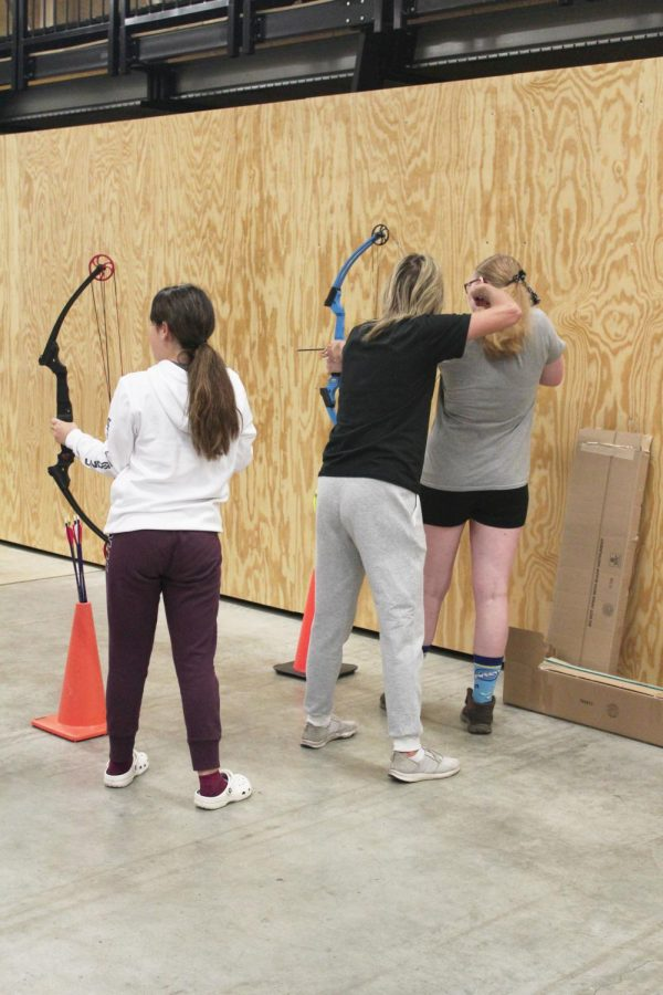 P.E teacher Lisa Antonowich helps freshman Hailey Ryan with her aim.