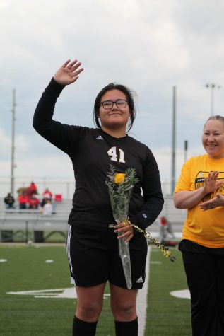 Senior Valery Landrum holds a flower while waving to the crowd after being recognized.