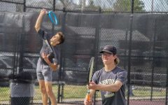 Senior Jonah Schloneger jumps in order to hit the tennis ball while sophomore Justin Franz prepares for his next strike.