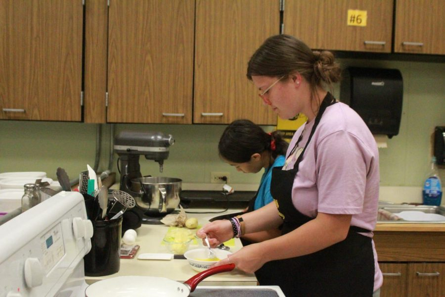 Senior Kaitlyn McMullin whisks eggs in Culinary Arts while her group member, senior Georgia Garcia slices potatos for hash browns.