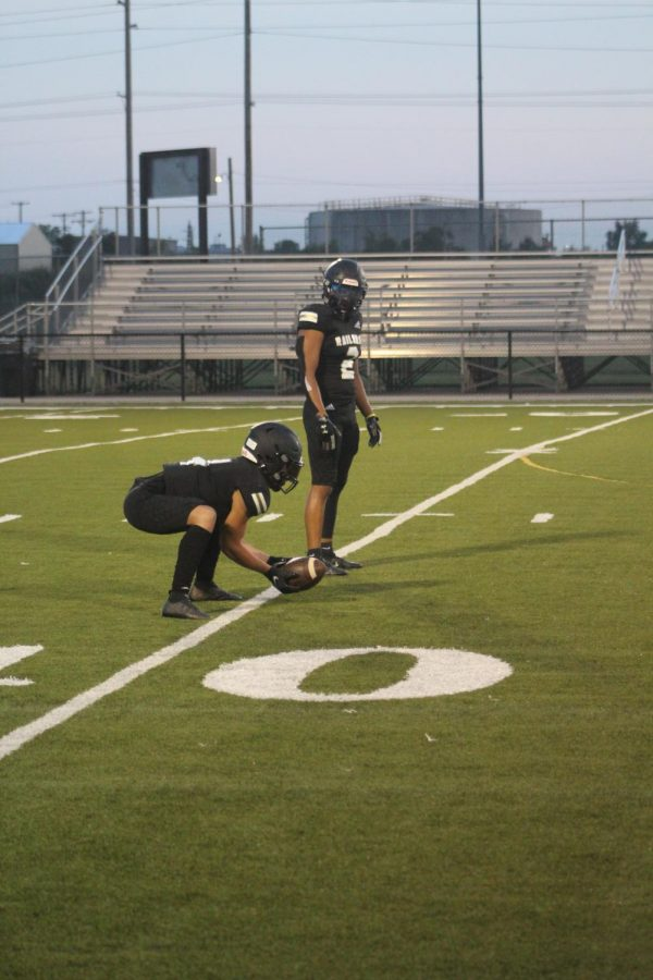 In+a+squatting+position+senior+Jonah+Remsberg+practices+catching+with+senior+Ben+Reyes+and+other+teammates.+