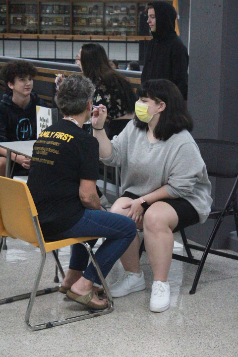 Senior Noelle Buentello paints a staff members face during GDFFD [Gold Day Friday Fun Day] on Aug. 20. GDFFD took place all throughout the commons and had music, games, face painting and more.