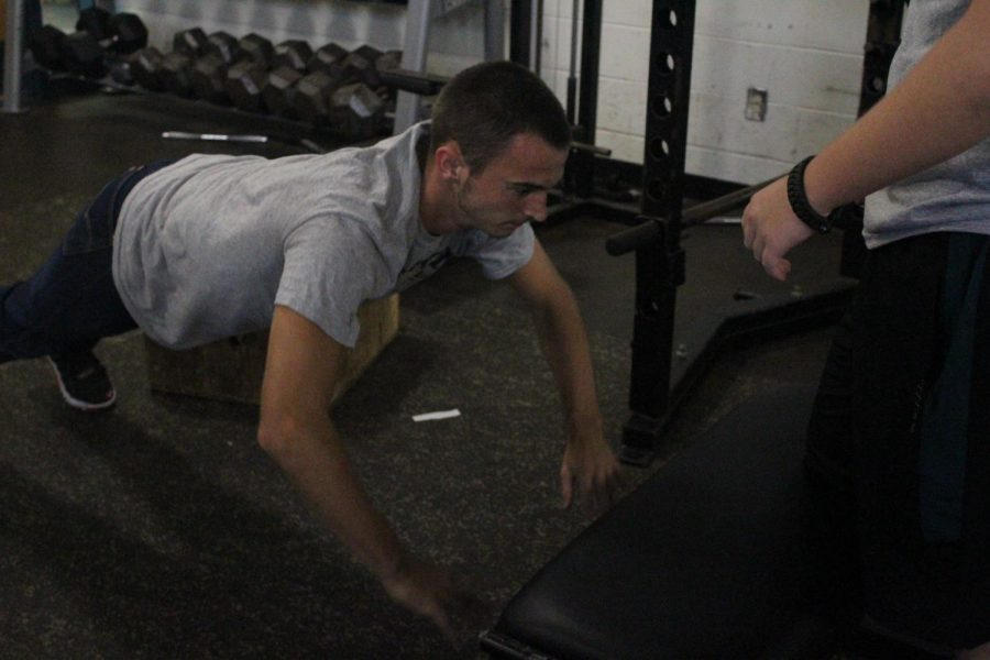 Sophomore Ryan Terbovich gets a good workout in while his partner, Wyatt Higgins, waits his turn during Weights on Aug. 26