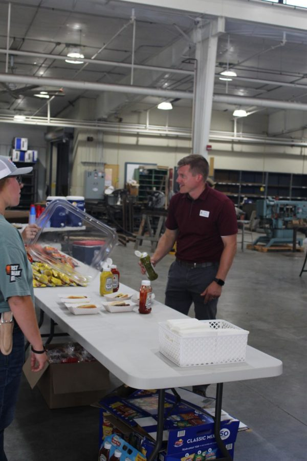 Staff member Ben Reed has a conversation with the people running the food table while he prepares to put relish on his hot dog.
