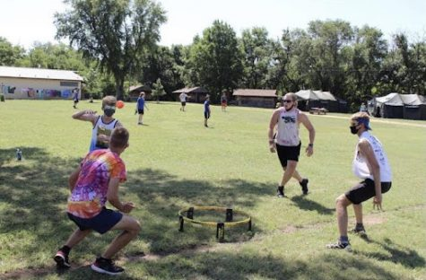 Senior Kaden Anderson and junior Simon Koontz play spike ball with their counselors during interest group time at camp Mennoscah.