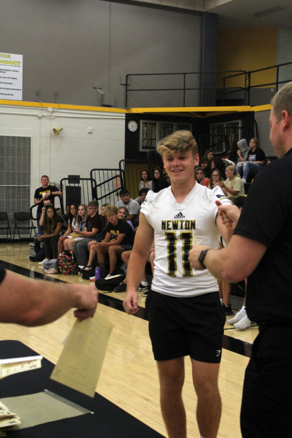 Senior Ben Crawford gave a fist bump to principal Caleb Smith while he was handed his award from assistant principal Derek Bristol.