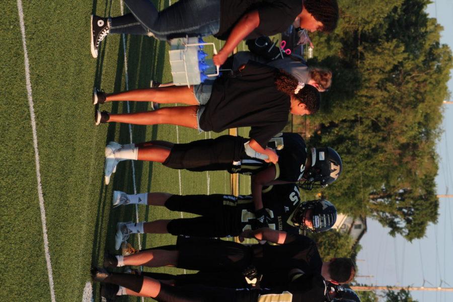 Freshman Cadalina Blasi hands players their water bottles.