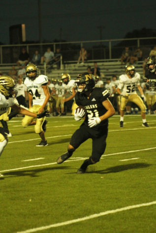 Trying to run the ball down the field, junior Dylan Mcbee avoids his opponent.