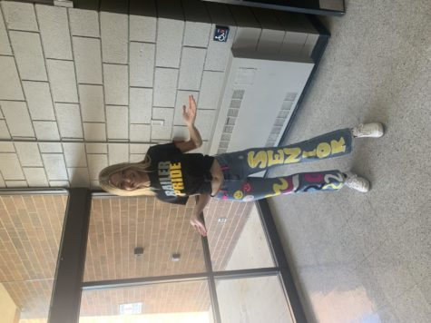 Senior Hallie Watkins poses for a picture with hand painted jeans on railer  pride day.