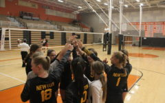 At a timeout the JV volleyball team finishes the huddle with a breakdown.