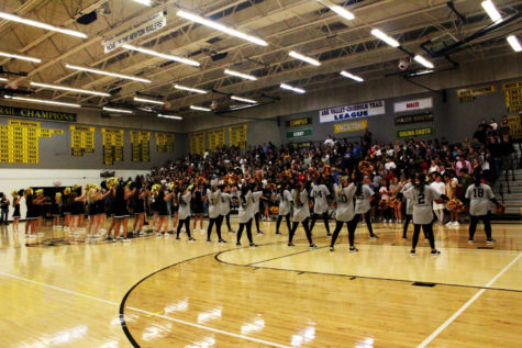 The cheer and dance team cheer with the students to get the pep assembly going.