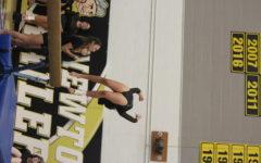 Junior Elisa Fernandez dismounts off the beam to end her routine.