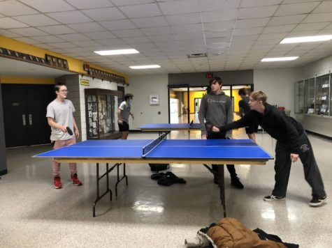 Students gather together to start a game of ping pong.