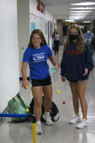 Freshmen Natalie Hershberger Margaret Oswald play a game of ladder toss by the P. E classroom.