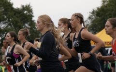 Keeping up with the pack, junior Jaymie Murry runs alongside other competitors. The meet was held Saturday, Oct. 2, at Centennial Park.
