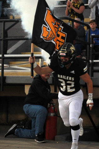 Leading the football team out of the locker senior Clayton Smith carries the Newton High School flag.