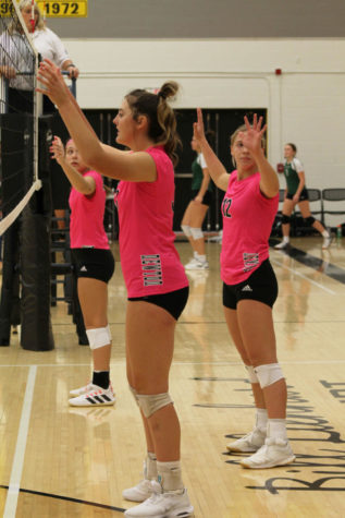 Preparing to block the ball, junior Tegan Livesay lifts her arms and watches the upcoming serve.